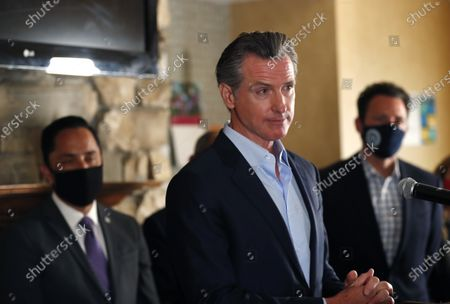Stock Photo of sGovernor Gavin Newsom speaks at a news conference about a $12 billion package bolstering the state's response to the homelessness crisis at the Kearney Vista Apartments, which houses homeless people in a converted hotel on Tuesday, May 11, 2021 in San Diego, CA. San Diego Mayor Todd Gloria, left, and Supervisor Nathan Fletcher look on.