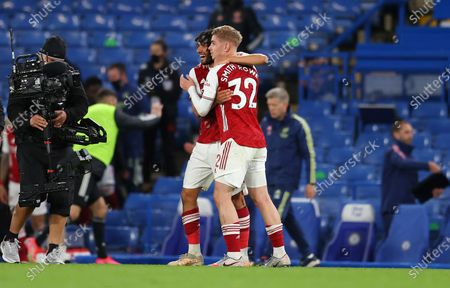 Arsenal's Emile Smith Rowe, right, celebrates with his teammate Mohamed Elneny after winning the English Premier League soccer match between Chelsea and Arsenal at Stamford Bridge stadium in London, England