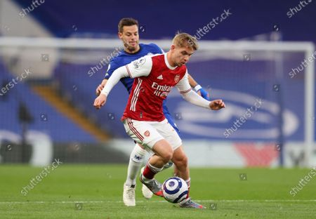 Arsenal's Emile Smith Rowe, foreground, challenges for the ball with Chelsea's Hakim Ziyech during the English Premier League soccer match between Chelsea and Arsenal at Stamford Bridge stadium in London, England