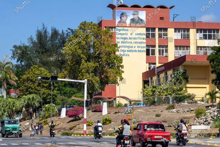 Traffic and lifestyle in Avenida Garzon. Building of CODESA with the images of Fidel Castro and Raul Castro, Santiago de Cuba, Cuba