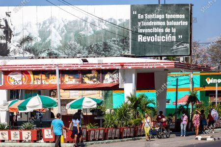 Stock Image of Dinos Pizza with a billboard reading a short phrase by Fidel Castro. Cuban real people walk in the area, Santiago de Cuba, Cuba