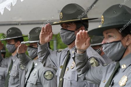 Mississippi Department of Wildlife, Fisheries and Parks officers Capt. Megan Fedrick, right, Major Scottie Jones, center and Conservation Officer Mark Bowles, left, salute during the playing of The National Anthem at the beginning of the agency's Fallen Officers Memorial Service, at headquarters in Jackson, Miss. The ceremony honors those lawmen who gave their lives in the line of duty
