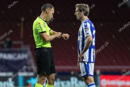 Guillermo Cuadra Fernandez, referee of the match talks with Nacho Monreal of Real Sociedad during La Liga football match played between Atletico de Madrid and Real Sociedad SAD at Wanda Metropolitano stadium on May 12, 2021 in Madrid, Spain.