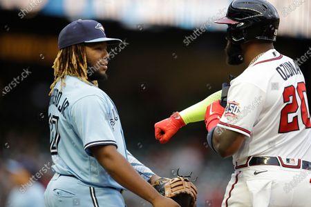 Toronto Blue Jays' Vladimir Guerrero Jr., left, speaks with Atlanta Braves' Marcell Ozuna during a baseball game, in Atlanta