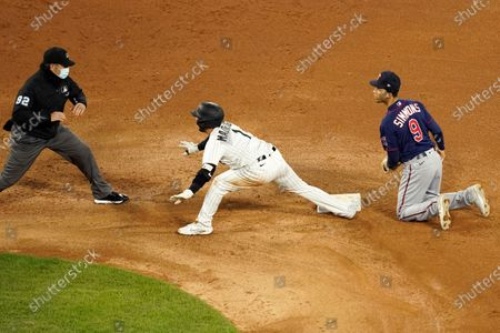 Chicago White Sox's Nick Madrigal (1) looks to second base umpire James Hoye for the safe sign on his double as Minnesota Twins' Andrelton watches during the fourth inning of a baseball game, in Chicago