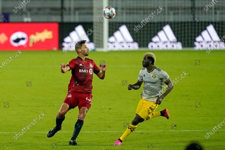 Toronto FC defender Omar Gonzalez, left, heads the ball away from Columbus Crew forward Gyasi Zerdes during the second half of an MLS soccer match, in Orlando, Fla