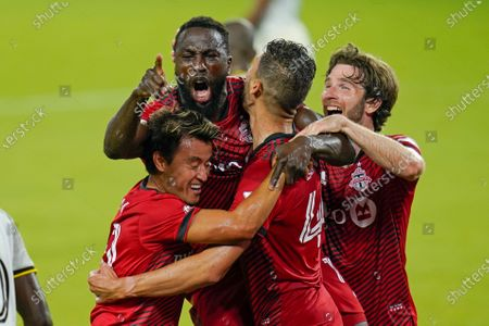 Toronto FC forward Jozy Altidore, center, celebrates after scoring a goal against the Columbus Crew with teammates from left, forward Tsubasa Endoh, defender Omar Gonzalez and forward Patrick Mullins during the second half of an MLS soccer match, in Orlando, Fla