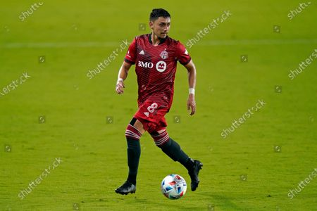 Toronto FC midfielder Marco Delgado (8) moves the ball against the Columbus Crew during the second half of an MLS soccer match, in Orlando, Fla