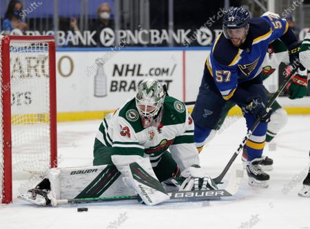 Minnesota Wild goaltender Cam Talbot (33) makes a stick save as St. Louis Blues' David Perron (57) looks for the loose puck in the second period of an NHL hockey game, in St. Louis