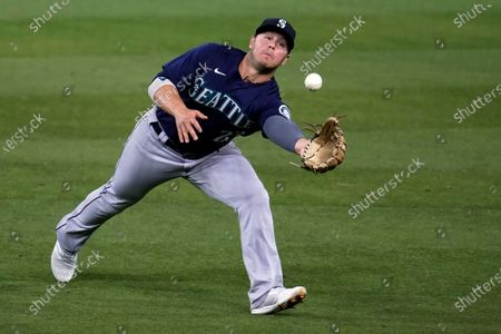 Seattle Mariners second baseman Ty France reaches for but can't catch a fly ball from Los Angeles Dodgers' Will Smith during the fourth inning of a baseball game, in Los Angeles. Smith got a single on the play