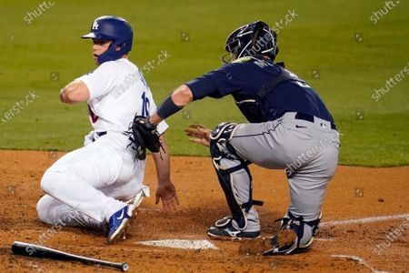 Seattle Mariners catcher Tom Murphy, right, tags out Los Angeles Dodgers' Will Smith at home plate on a grounder by Gavin Lux during the fourth inning of a baseball game, in Los Angeles