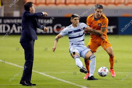 Houston Dynamo head coach Tab Ramos, left, yells from the sidelines as Sporting Kansas City forward Alan Pulido (9) passes the ball in front of defender Zarek Valentin (4) during the second half of an MLS soccer match, in Houston