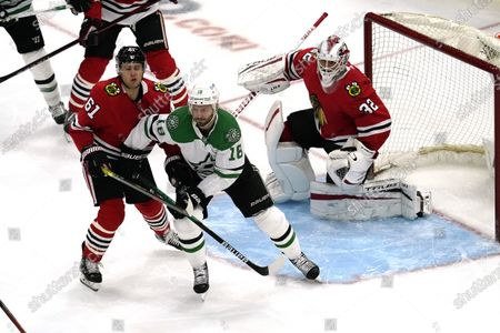 Dallas Stars center Jason Dickinson (18) and Chicago Blackhawks defenseman Ian Mitchell (51) battle as they watch the puck during the first period of an NHL hockey game in Chicago