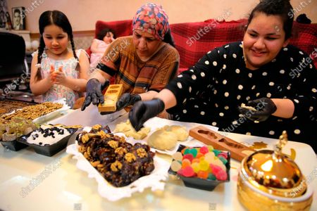 Stock Image of Family prepares cookies during the first day of Eid al-Fitr holiday in Basra, Iraq, . Eid al-Fitr marks the end of the Muslims' holy fasting month of Ramadan