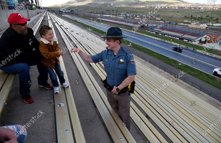 """Colorado State Patrol Trooper Josh Lewis fist bumps 3-year-old Lincoln Delagarza, of Northglenn, Colorado, before racing begins at Bandimere Speedway west of Denver on . The State Patrol runs a program called """"Take it to the Track"""" in hopes of luring racers away from public areas to a safer and more controlled environment, even allowing participants to race a trooper driving a patrol car. The program's goals have gained new importance and urgency this year as illegal street racing has increased amid the coronavirus pandemic"""