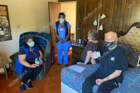 Stock Image of John McFarland, 70, shows his vaccination card after receiving the COVID-19 vaccine inside his bedroom in Hayward, Calif., . Alameda County nurses Patricia Calloway, left, and Devette Laflore chat with his wife, Patti Amaral, 73, while they waited to make sure there were no vaccine side effects. As interest in vaccinations dwindles statewide and nationally, local health offices and other providers are ramping up efforts to find and reach millions of people in the U.S. who cannot leave their homes or who need help with transportation