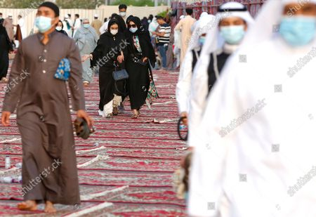 Muslim women, center rear, wearing masks to curb the spread of coronavirus outbreak, walk on carpets after they performed Eid al-Fitr prayer marking the end of the holy fasting month of Ramadan at al-Mirabi Mosque in Jiddah, Saudi Arabia