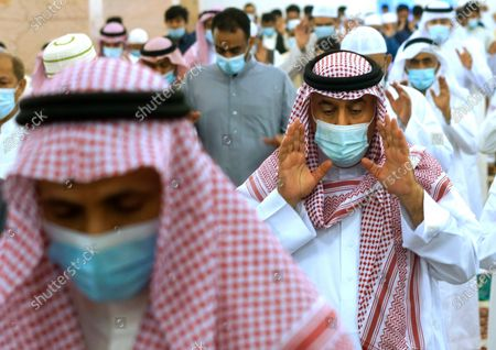 Saudis wear masks and keep social distancing, to curb the spread of coronavirus as they perform Eid al-Fitr prayer marking the end of the holy fasting month of Ramadan at al-Mirabi Mosque in Jiddah, Saudi Arabia
