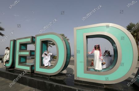 Stock Picture of Children play on an outdoor display that reads, Jeddah, as they celbrate Eid al Fitr prayer marking the end of the holy fasting month of Ramadan in Jiddah, Saudi Arabia