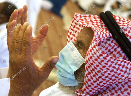 Stock Photo of Saudi worshipper wears a mask to curb the spread of coronavirus outbreak, as he performs Eid al-Fitr prayer marking the end of the holy fasting month of Ramadan at al-Mirabi Mosque in Jiddah, Saudi Arabia