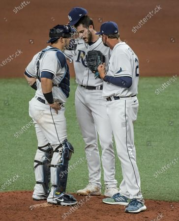 Tampa Bay Rays catcher Mike Zunino (L) and pitching coach Kyle Snyder (R) talk to reliever Ryan Thompson during the seventh inning of a baseball game against the New York Yankees at Tropicana Field in St. Petersburg, Florida on Wednesday, May 12, 2021. Photo by Steven J. Nesius/UPI