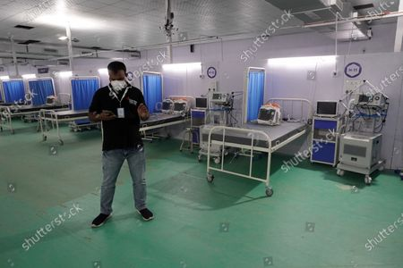 A volunteer stands next to beds at the site of a temporary COVID-19 care facility, amidst the rising number of the coronavirus cases, at Ramlila grounds, in New Delhi, India on May 13, 2021. India's daily case count of Covid-19 went past the 3.5 lakh mark on Thursday after a two-day low even as the country recorded more than 4,000 deaths for the second day in a row.