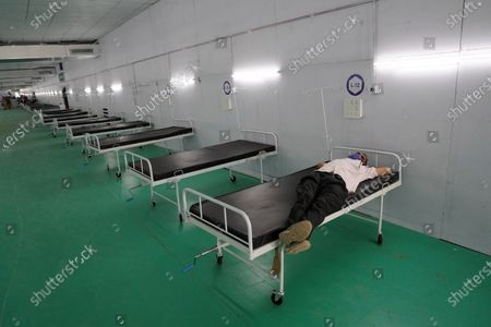 A worker stretches over one of the beds at the site of a temporary COVID-19 care facility, amidst the rising number of the coronavirus cases, at Ramlila grounds, in New Delhi, India on May 13, 2021. India's daily case count of Covid-19 went past the 3.5 lakh mark on Thursday after a two-day low even as the country recorded more than 4,000 deaths for the second day in a row.
