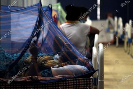 Stock Image of A covid-19 patient is seen at a makeshift facility created inside a sports complex, amidst the spread of coronavirus cases, in New Delhi, India on May 13, 2021. India's daily case count of Covid-19 went past the 3.5 lakh mark on Thursday after a two-day low even as the country recorded more than 4,000 deaths for the second day in a row.