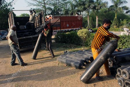 Stock Photo of Workers unload oxygen cylinders from a truck at a makeshift facility created inside a sports complex, amidst the spread of coronavirus cases, in New Delhi, India on May 13, 2021. India's daily case count of Covid-19 went past the 3.5 lakh mark on Thursday after a two-day low even as the country recorded more than 4,000 deaths for the second day in a row.