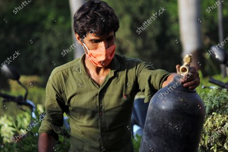 A worker unloads an oxygen cylinder from a truck at a makeshift facility created inside a sports complex, amidst the spread of coronavirus cases, in New Delhi, India on May 13, 2021. India's daily case count of Covid-19 went past the 3.5 lakh mark on Thursday after a two-day low even as the country recorded more than 4,000 deaths for the second day in a row.