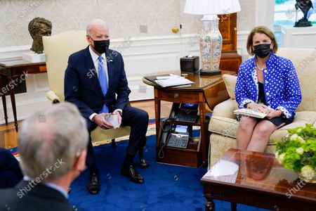 President Joe Biden speaks during a meeting in the Oval Office of the White House, in Washington. Sen. Shelley Moore Capito, R-W.Va., right, and Sen. Mike Crapo, R-Idaho listen