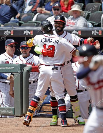 Atlanta Braves' Marcell Ozuna congratulates Ronald Acuna Jr. (13) after Acuna hit a home run off Toronto Blue Jays' Ross Stripling in the first inning of a baseball game, in Atlanta