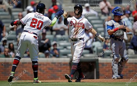 Atlanta Braves' Dansby Swanson, center, celebrates with Marcell Ozuna (20) after hitting a two run home run off Toronto Blue Jays' Ryan Borucki in the sixth inning of a baseball game, in Atlanta