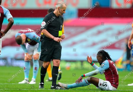Referee Martin Atkinson (L) shows the yellow card to Aston Villa's Bertrand Traore (down) during the English Premier League soccer match between Aston Villa and Everton FC in Birmingham, Britain, 13 May 2021.