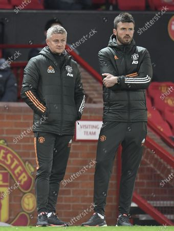 Manchester United's manager Ole Gunnar Solskjaer (L) and his assistant Michael Carrick (R) react during the English Premier League soccer match between Manchester United and Liverpool FC in Manchester, Britain, 13 May 2021.