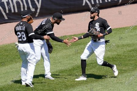 Stock Picture of Chicago White Sox's Leury Garcia (28) and Yoan Moncada, center, greet Billy Hamilton outside the dugout after Hamilton's leaping catch of Minnesota Twins' Kyle Garlick's deep fly ball with the bases loaded during the fourth inning of a baseball game, in Chicago
