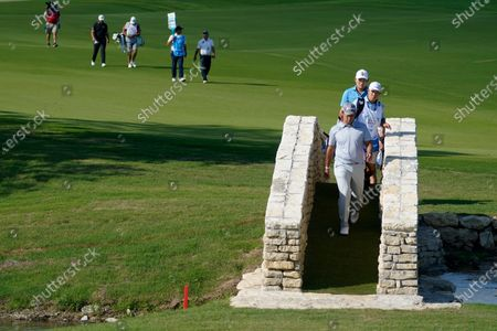 Hideki Matsuyama of Japan walks onto the 18th green followed by Sung Kang, rear, during the first round of the AT&T Byron Nelson golf tournament in McKinney, Texas