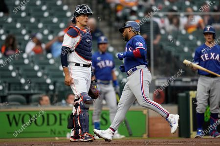 Texas Rangers' Willie Calhoun, right, scores after hitting a home run as Houston Astros catcher Jason Castro looks on during the first inning of a baseball game, in Houston