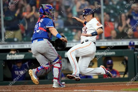 Houston Astros' Jason Castro (18) scores as Texas Rangers catcher Jose Trevino waits for the throw during the second inning of a baseball game, in Houston
