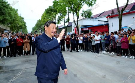 Chinese President Xi Jinping, also general secretary of the Communist Party of China Central Committee and chairman of the Central Military Commission, waves to villagers while inspecting Zouzhuang Village, Xichuan County, Nanyang, Central China's Henan Province, May 13, 2021.