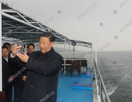 Stock Photo of Chinese President Xi Jinping, general secretary of the Communist Party of China Central Committee and chairman of the Central Military Commission, inspects the Danjiangkou Reservoir and listens to introductions to the construction, management and operation of the middle route of the South-to-North Water Diversion Project, and the ecological conservation of the water source region in Xichuan County, Nanyang, Central China's Henan Province, May 13, 2021.