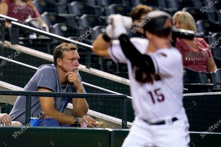 Former Arizona Diamondbacks pitcher and MLB Hall of Fame inductee, Randy Johnson, left, watches the Diamondbacks during the sixth inning of a baseball game against the Miami Marlins as Diamondbacks' Andrew Young waits to bat, in Phoenix