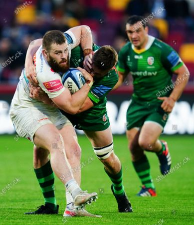 Luke Cowan-Dickie of Exeter Chiefs holds off a tackle from George Nott of London Irish