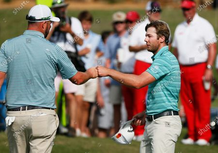 Marc Leishman, left, and Sam Burns, right, fist-bump on the 18th green following their second round of the AT&T Byron Nelson golf tournament in McKinney, Texas