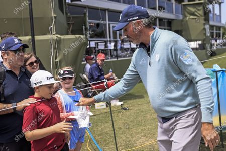 Matt Kuchar of the US (R) hands an autographed glove to a young fan during the second round of the AT&T Byron Nelson golf tournament at TPC Craig Ranch in McKinney, Texas, USA, 14 May 2021. The tournament is being played 13 May through 16 May.