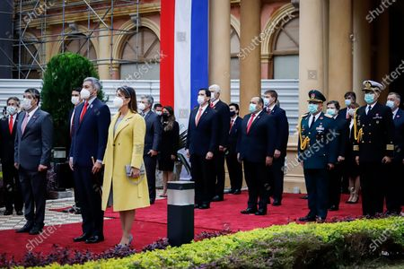 Hugo Velázquez (L), vice president of Paraguay, Mario Abdo Benítez (C), president of Paraguay, Silvana Lopez Moreira (R), first lady of Paraguay and other authorities during the raising of the flag, at the Government Palace in Asuncion, Paraguay, 14 May 2021. Paraguay commemorated its 210th anniversary of independence this Friday, the second during the pandemic, with an official celebration in the Government Palace and the subsequent tedeum in the Cathedral with the presence of the president, Mario Abdo Benitez, and members of his Government. During the religious ceremony, the Archbishop of Asunción, Edmundo Valenzuela, delivered a homily with political and social overtones, in which he alluded to the 'pandemic and corruption'.