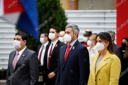 Hugo Velázquez (L), vice president of Paraguay, Mario Abdo Benítez (C), president of Paraguay and Silvana Lopez Moreira (R), first lady during the raising of the flag, at the Government Palace in Asuncion, Paraguay, 14 May 2021. Paraguay commemorated its 210th anniversary of independence this Friday, the second during the pandemic, with an official celebration in the Government Palace and the subsequent tedeum in the Cathedral with the presence of the president, Mario Abdo Benitez, and members of his Government. During the religious ceremony, the Archbishop of Asunción, Edmundo Valenzuela, delivered a homily with political and social overtones, in which he alluded to the 'pandemic and corruption'.