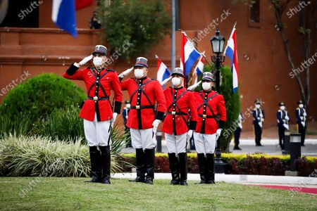 Soldiers participate in the raising of the flag during the commemoration of the 210 years of Paragua's independence, at the Government Palace in Asuncion, Paraguay, 14 May 2021. Paraguay commemorated its 210th anniversary of independence this Friday, the second during the pandemic, with an official celebration in the Government Palace and the subsequent tedeum in the Cathedral with the presence of the president, Mario Abdo Benitez, and members of his Government. During the religious ceremony, the Archbishop of Asunción, Edmundo Valenzuela, delivered a homily with political and social overtones, in which he alluded to the 'pandemic and corruption'.