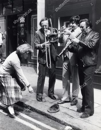 Chris Barber, Kenny Ball and Acker Bilk are seen busking on the street.