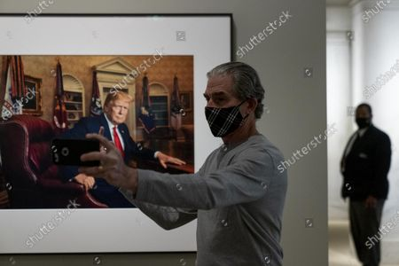 A man who identified himself only as Jeff, gestures with his middle finger as he takes a selfie with a photograph of former President Donald Trump by Pari Dukovic as it hangs in the America's Presidents exhibition at the Smithsonian's National Portrait Gallery in Washington
